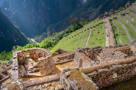 Panoramic view on the ceremonial Temple of the Sun build by Incas on the Machu Picchu mountain. Archaeological site with green agricultural terraces.  Popular tourist attraction.