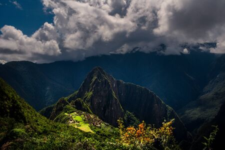 Majestic aerial view on the Machu Picchu  Huayna Picchu mountain with Incan sacred city ruins during the sunset. Beautiful greenery in the foreground.