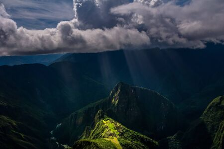 Epic and unique aerial view on the Machu Picchu  Huayna Picchu mountain with Incan sacred city ruins during the sunset. Dramatic clouds with sun rays passing trough. Verical. Stock fotó