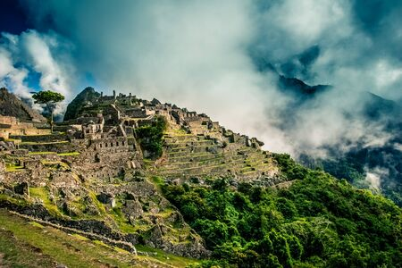 Mystical view on the Machu Picchu city ruins covered with dramatic clouds. Sacred city of Inca during the sunset.