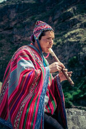 Cusco  Peru - May 29.2008: Portrait of a man, shepherd, goat herder, dressed up in native, peruvian costume seating on the rock and playing on the flute in the mountains.