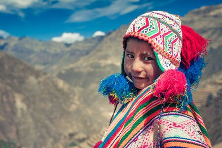 Cusco  Peru - May 29.2008: Portrait of a  boy smiling, dressed up in colorful native peruvian costume standing on the hill in the mountains.