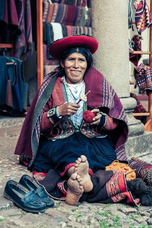 Cusco  Peru - May 26.2008: Portrait of a sewer woman, seamstress, dressed up in traditional native peruvian clothes. Seating on the street with barefoot, holding sewing tools while smiling. Sajtókép