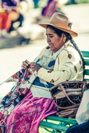 Cusco  Peru - May 26.2008: Portrait of a  indigenous woman, dressed up in traditional native peruvian clothes and hat. Seating on the bench holding the sewing tools during the sunny day. Sajtókép