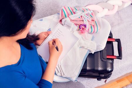 Pregnant woman doing the checklist while packing the suitcase with newborn baby clothes for the hospital.