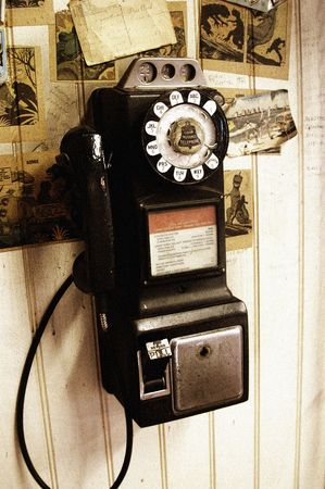 this image of an antique Payphone is tinted slightly to create an old rustic look. Film noise effect is intentionally added into the picture.