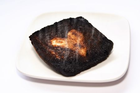 burnt toast: Badly burnt Toast safe for the middle heart-shaped part. Conceptual for failed relationship, broken-hearts, bad experience with love, etc.