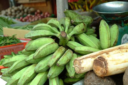 combs of raw green banana on sale in an Asian market