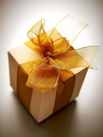 A small box of appreciation gift. Golden yellow tinted to enhance the mood. Shallow depth of field shot is intentional. Stock Photo