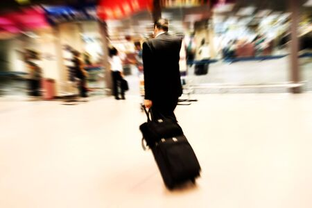 Business man rushing at the airport. Intentional Zoom-effect motion blur. Stock Photo