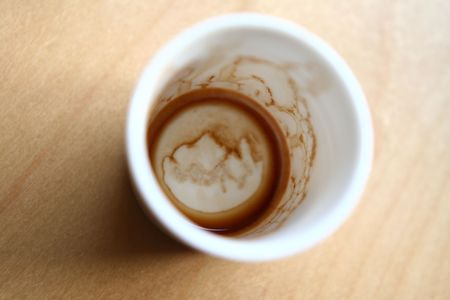 sip: Empty stained cup of coffee. Selective focusing is intentional.