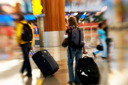 People rushing in an airport. Shot with a special effect lens. Intentional blur & selective focus.
