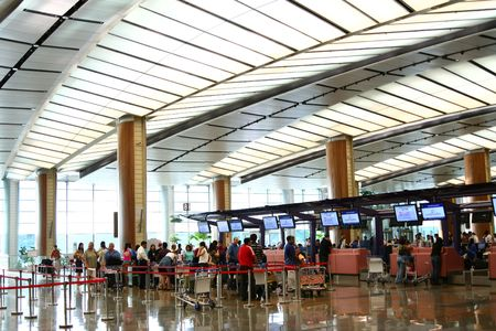 Airport scenes background series. Terminal two, Changi Airport Singapore. Travellers waiting to check-in. Editorial