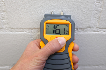 A male hand holding a yellow moisture meter in front of a wall