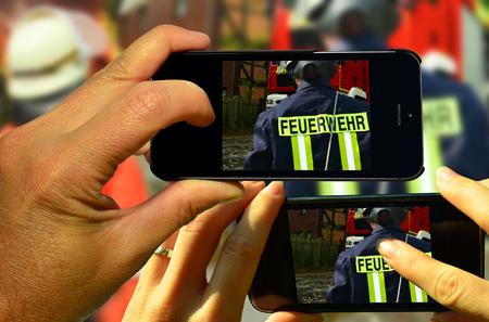 Los turistas fotografían a los bomberos durante el despliegue Foto de archivo - 80251182