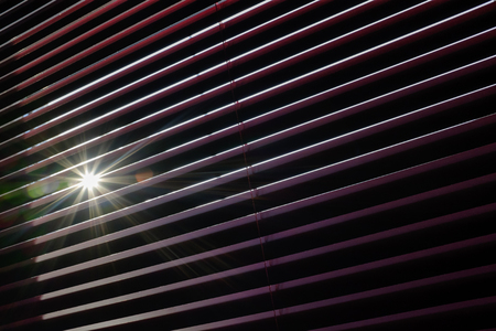 Bright sunrays through the slats of a blind