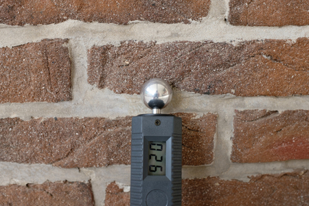 A male hand is holding a moisture meter to test the humidity of the wall