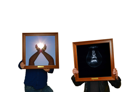 Two men are holding picture frame with sun and a lightbulb in the dark