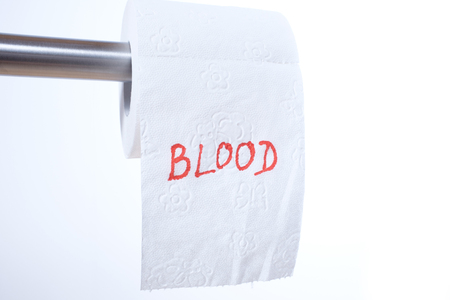 The word Blood in red letters on a toilet paper roll 스톡 콘텐츠