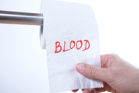 The word Blood in red letters on a toilet paper roll Standard-Bild