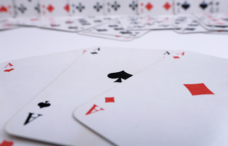 3 aces with other playing cards in the background Stock Photo
