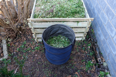A full compost box of wooden slats in the garden