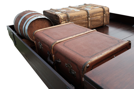 Antique suitcases and a barrel on a loading area of brown wood