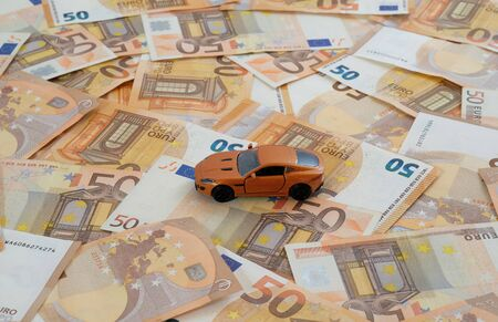 A model car on laid out 50 Euro banknotes as concept car costs