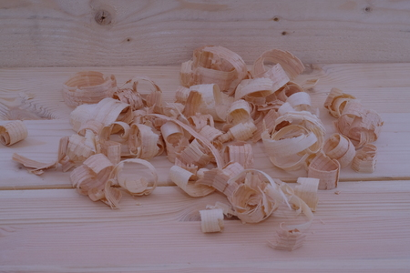Several planed wood shavings on boards in a wood workshop