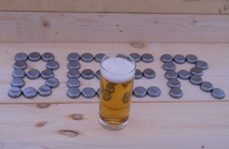 The word beer, with a bottle cap and a glass of beer