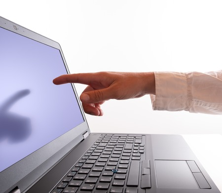 A man points with his forefinger to the computer monitor Stockfoto