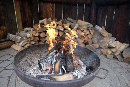 An open fire pit with firewood in the background Standard-Bild