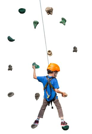 Young boy anxiously climbs a climbing wall