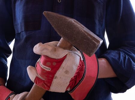 Detail of a handyman with hammer and work gloves Standard-Bild