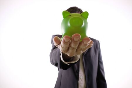 Bank employee with outstretched hand holding a green piggy bank Standard-Bild