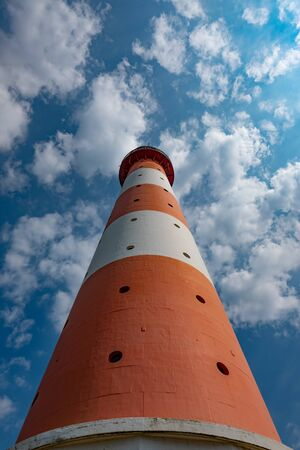 Shot of a red and white lighthouse with sky in the background Standard-Bild