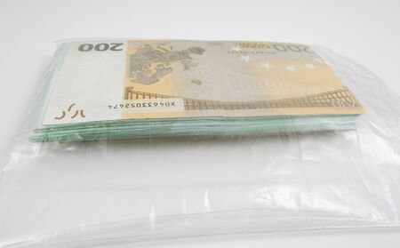 A large stack of money in a transparent plastic bag