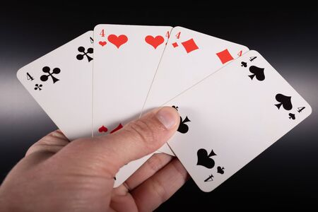Male hand holds three aces over black background