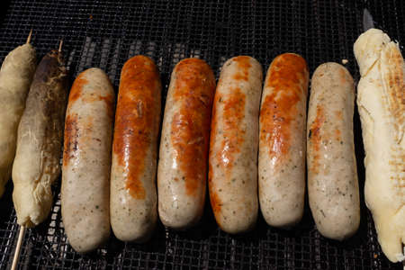 Sausages lying on a grill rack with skewered stick bread