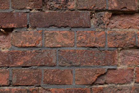 An old, peeled wall of red bricks.