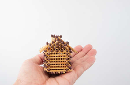 One hand holds a match house as an analogy to a home