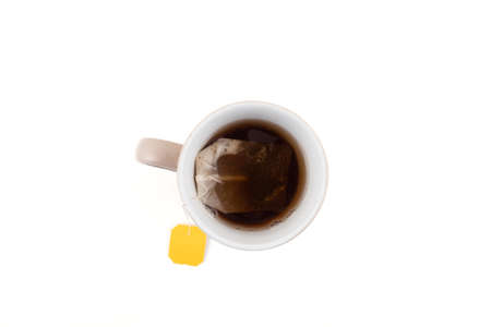 Tea cup with tea bag taken from above over white background.