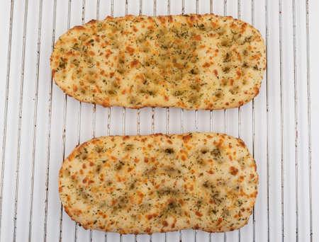 Two Italian focaccia flatbreads on an oven rack