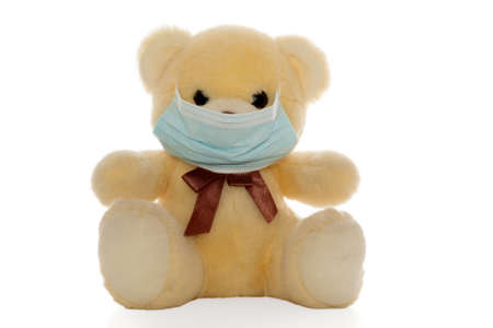 A fluffy plush bear with a face mask as a concept for a Covid-19 pandemic (isolated). Standard-Bild