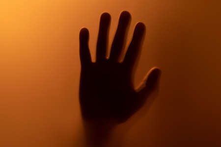 A creepy-looking hand shadow behind a blood-red illuminated frosted glass pane.