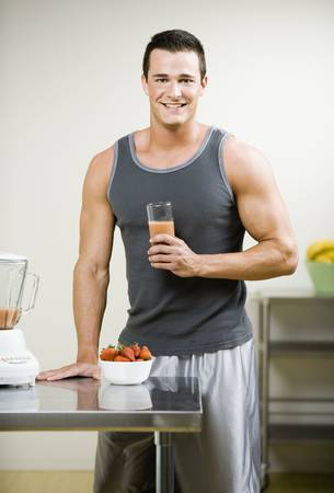 Muscular Young Man with Juice Smoothy Stock Photo