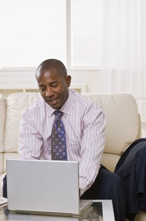 A businessman is sitting on a couch and working on a laptop.  He is looking away from the camera.  Vertically framed shot. Stock Photo - 5033481