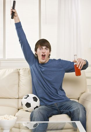 A young man is sitting on the couch in his living room and watching a sports game.  He is holding a remote control, a soda, and there is a soccer ball right next to him.  He is looking at the camera.  Vertically framed shot. photo