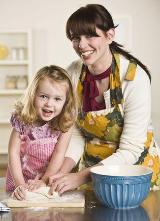 Un ni�o est� ayudando a una mujer algunos amasar masa para hacer pan. Est�n sonriendo a la c�mara. Verticalmente enmarcada disparo. Foto de archivo - 5033505