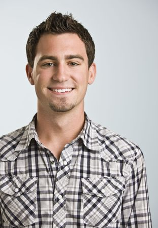 A young man wearing a plaid shirt is smiling at the camera. photo